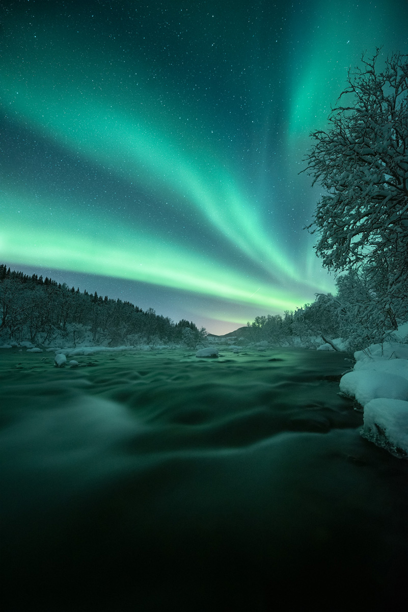 Display of Northern Lights above a half frozen river in Arctic Norway